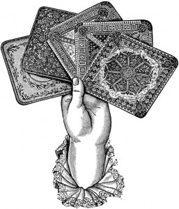 etching of woman's hand holding 5 old playing cards by Dover Publications